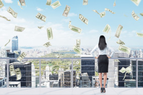 Young businesswoman with hands on hips standing on the roof of a business centre and looking at New York. Money falling from above. Back view. Concept of earning money.