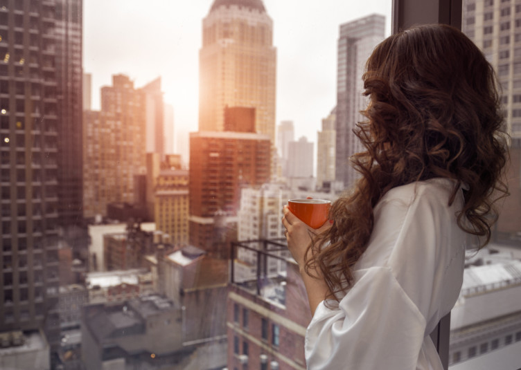Beautiful woman holding coffee cup and looking to the window in luxury Manhattan penthouse apartments. Good morning after wake up.