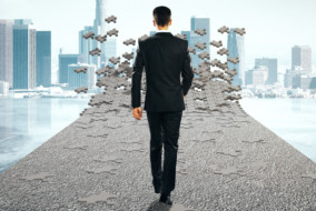 Success concept with businessman walking on road that is being assembled from puzzle pieces on city background. 3D Rendering